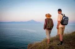 woman-man-top-mountain-sunset-men-backpacks-standing-enjoying-sea-view-57320851.jpg