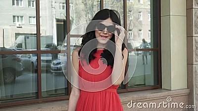Красивая девушка в красном платье и нося солнечных очках ...