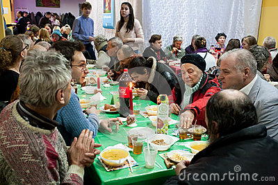 Elderly Women And Men Have A Food At The Christmas Charity