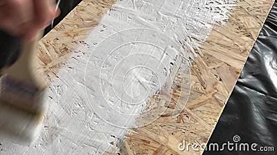 le processus de peindre une etagere en bois de panneau d osb dans le blanc sur un fond noir