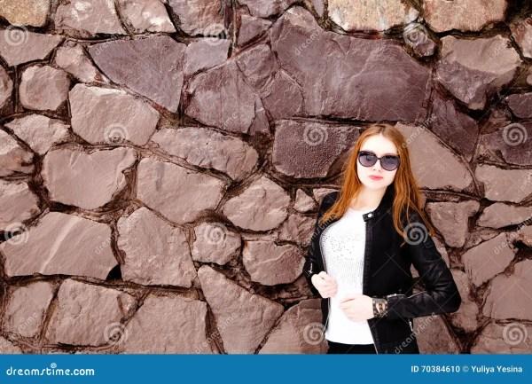Девушка в черных солнечных очках и куртке над кирпичной ...