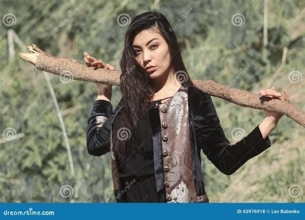 Женщина в национальном черном платье бархата с ручкой в ...