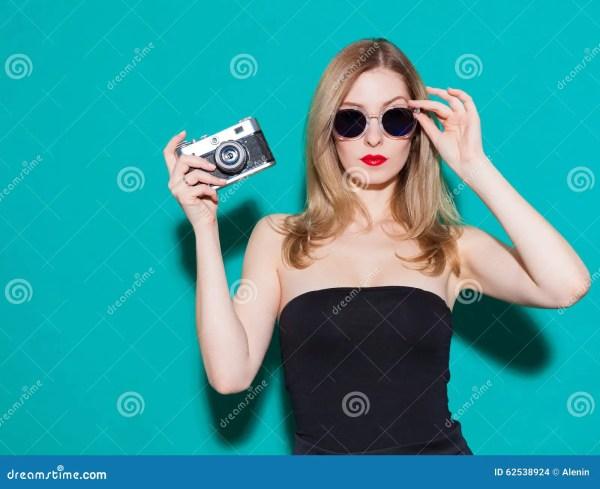Красивая модная девушка представляя и держа винтажную ...