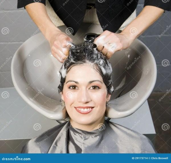 Привлекательная женщина получает шампунь и подготовлять ...