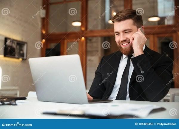 Счастливый молодой бизнесмен в черном костюме говоря на ...