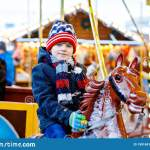 Adorable Little Kid Boy Riding On A Merry Go Round Carousel Horse At Christmas Funfair Or Market Outdoors Happy Child Stock Photo Image Of Joyful Ride 199168170