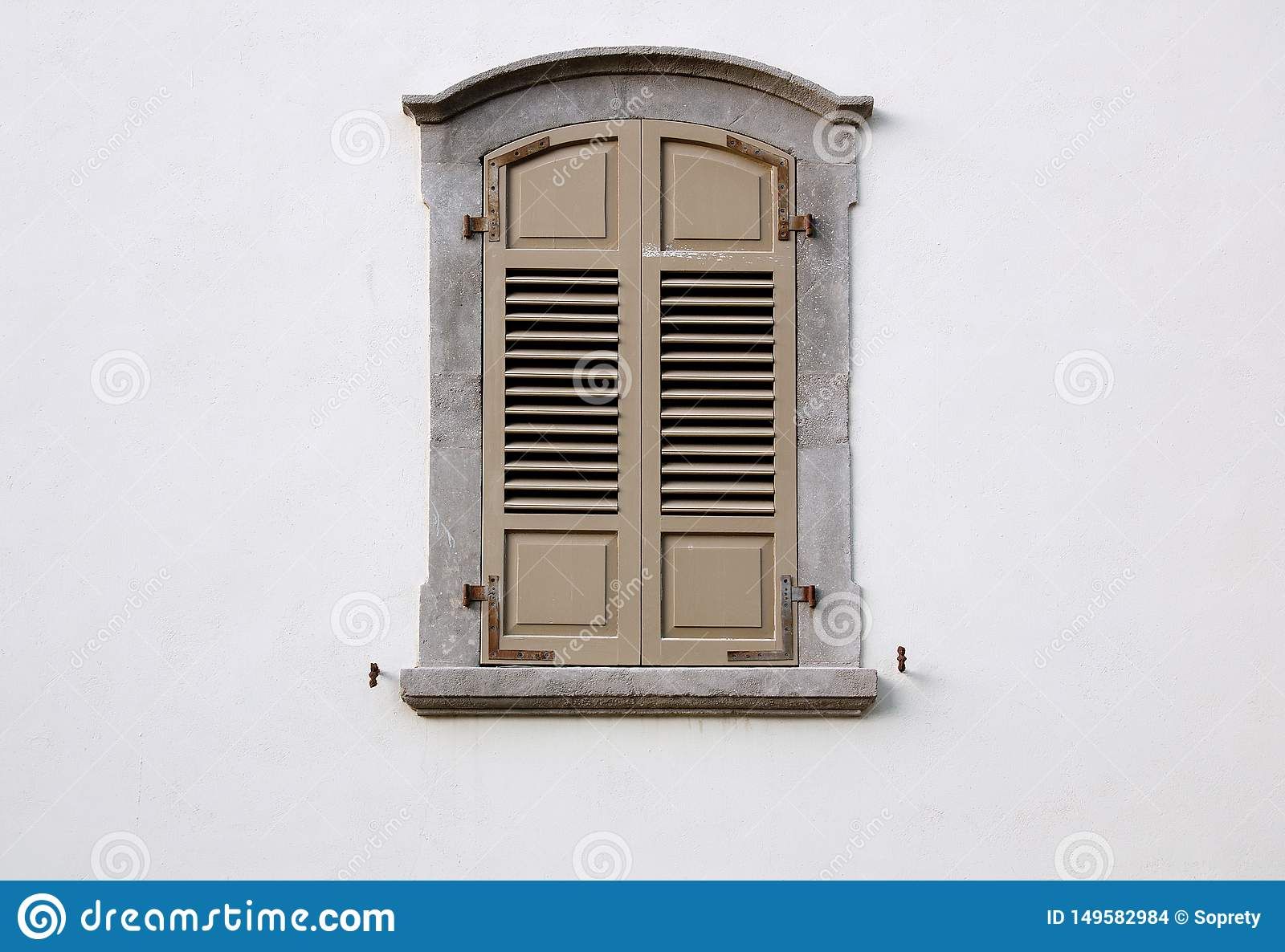Arched Window With Wooden Shutters On A White Wall Stock