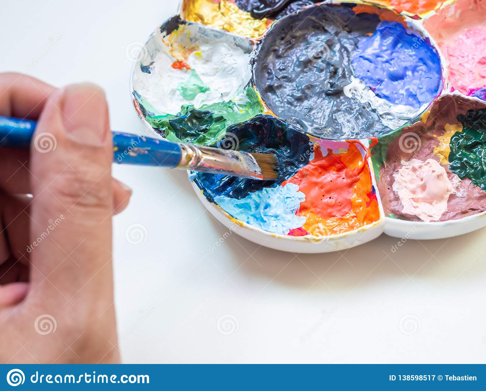 Artist Hand Mixing Acrylic Paint Color With Brush In