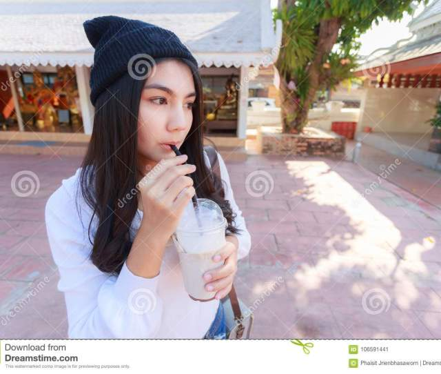 Asian Woman Drinking Coffee With Tube From Plastic Glass