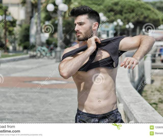 Attractive Muscular Young Man Undressing Taking Off Black T Shirt On Naked Ripped Torso And Removing It To Reveal Muscles On Chest Abs Arms