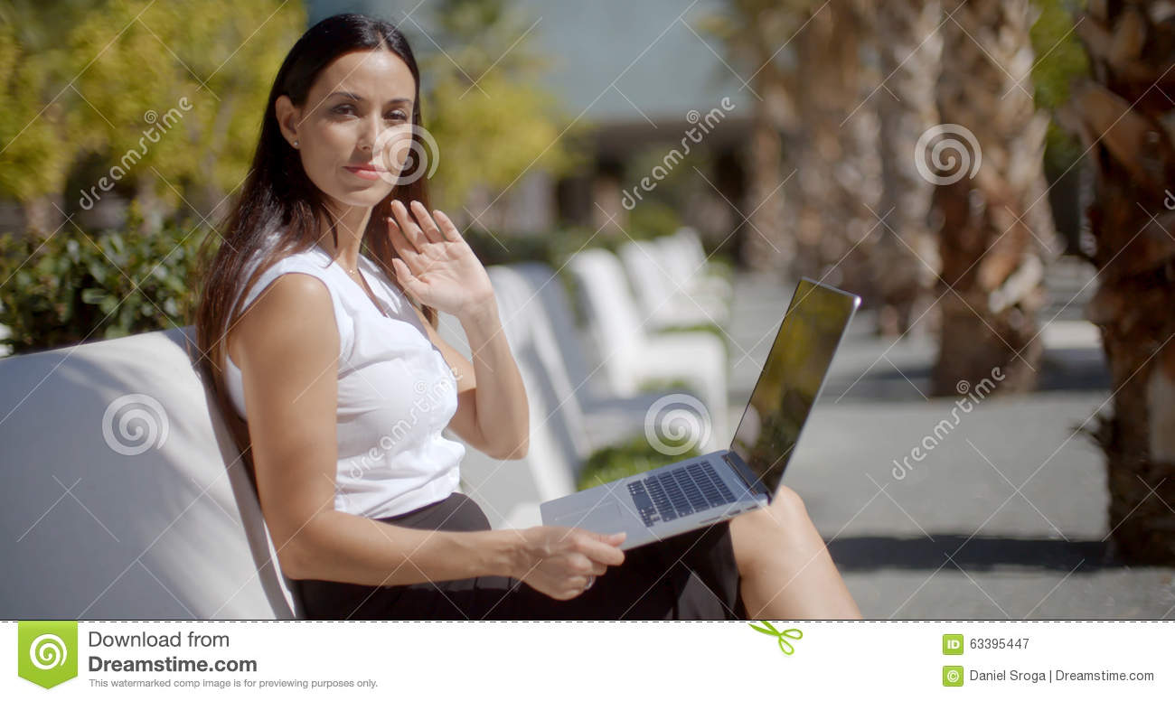Attractive Woman Sitting On A Bench With A Laptop Stock