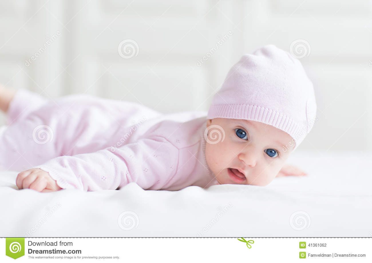 beautiful baby girl with big blue eyes in pink kni stock photo