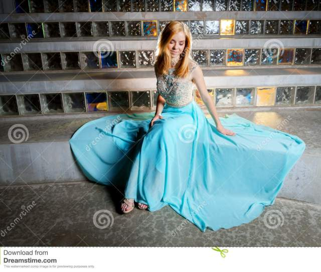 A Beautiful Blond Teen Girl Sits In Front Of Glass Block Admiring Her Prom Dress Which Is Spread Out Around Her She Looks Like A Princess