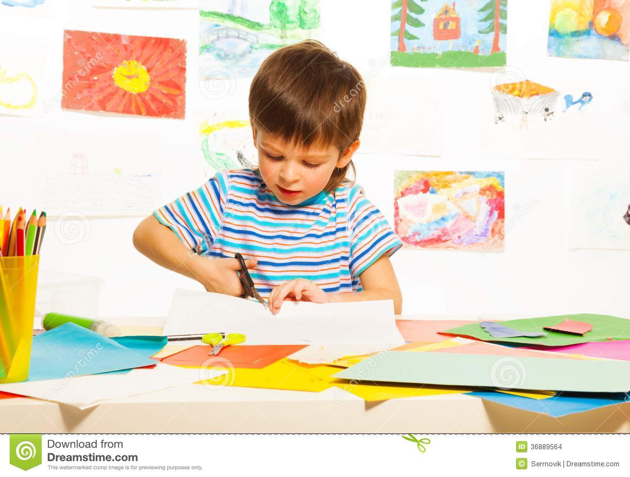Boy Cutting Paper With Scissors Stock Photo