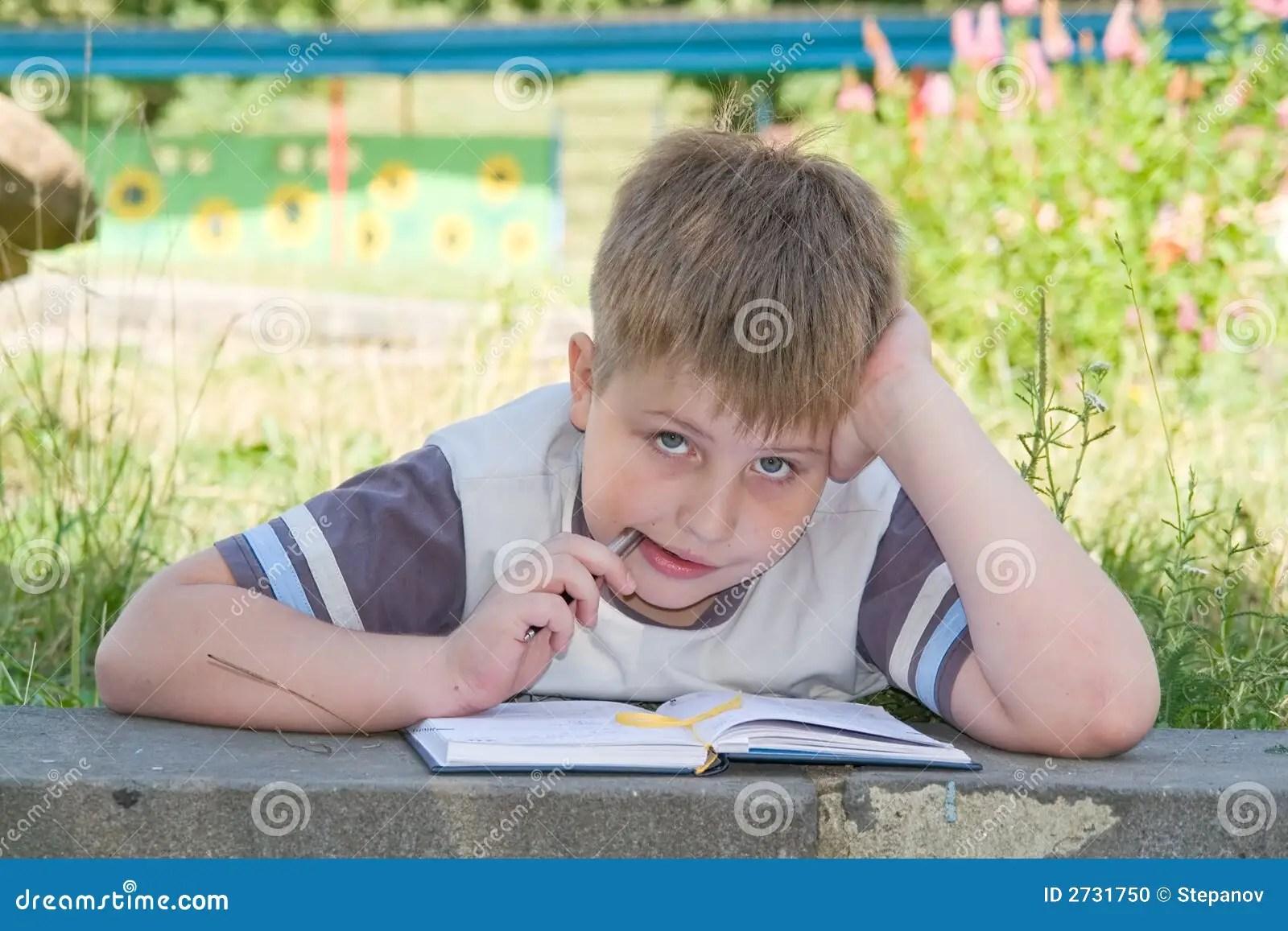 Boy Writes To Writing Books Stock Photo
