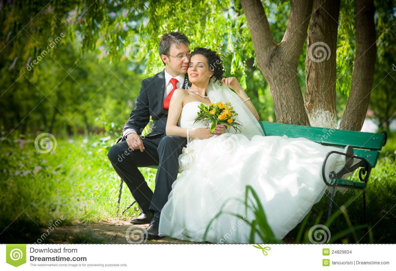Bride And Groom In A Park Sit On The Bench Stock Photo