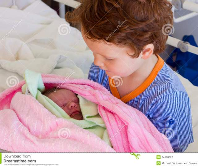 A Young Boy Meeting His Newborn Sister For The First Time In Hospital