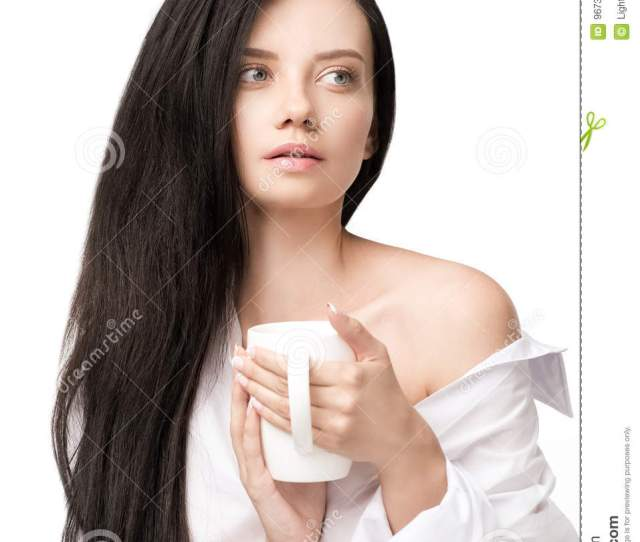 Brunette Girl In White Shirt Holding Cup With Hot Beverage And Looking Away