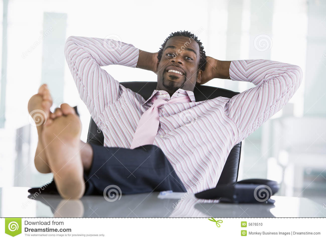 Businessman Sitting In Office With Feet On Desk Stock