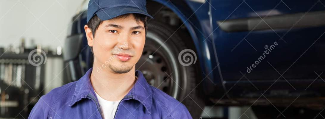 Confident Mechanic Standing At Repair Shop Stock Photo