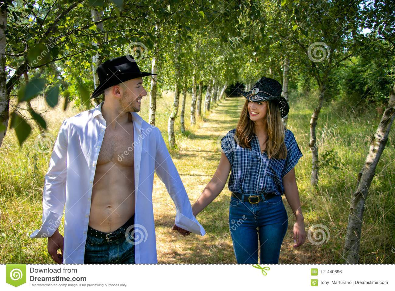 Cowboy And Cowgirl Couple With Hats Hold Hands As They