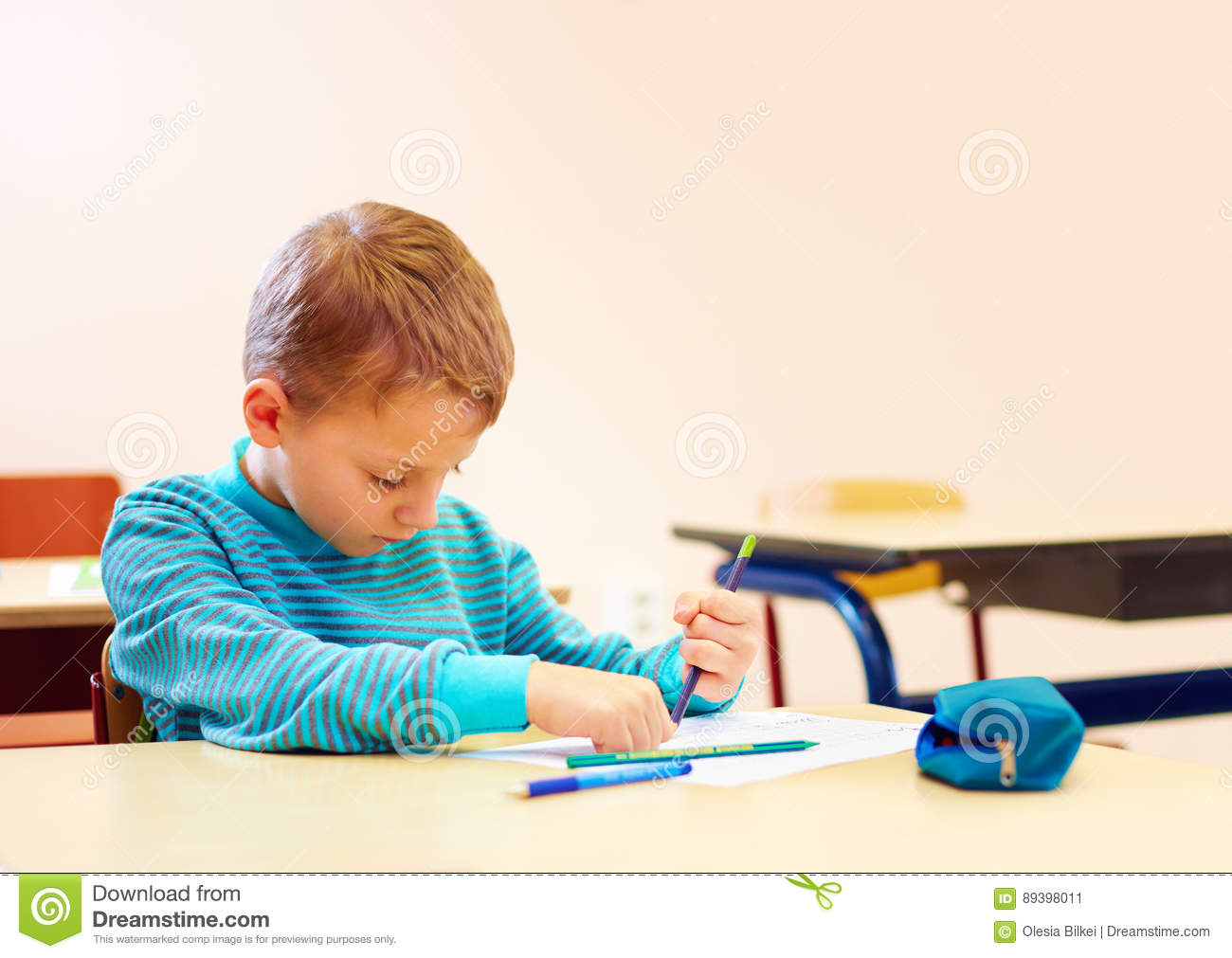 Cute Boy With Special Needs Writing Letters While Sitting