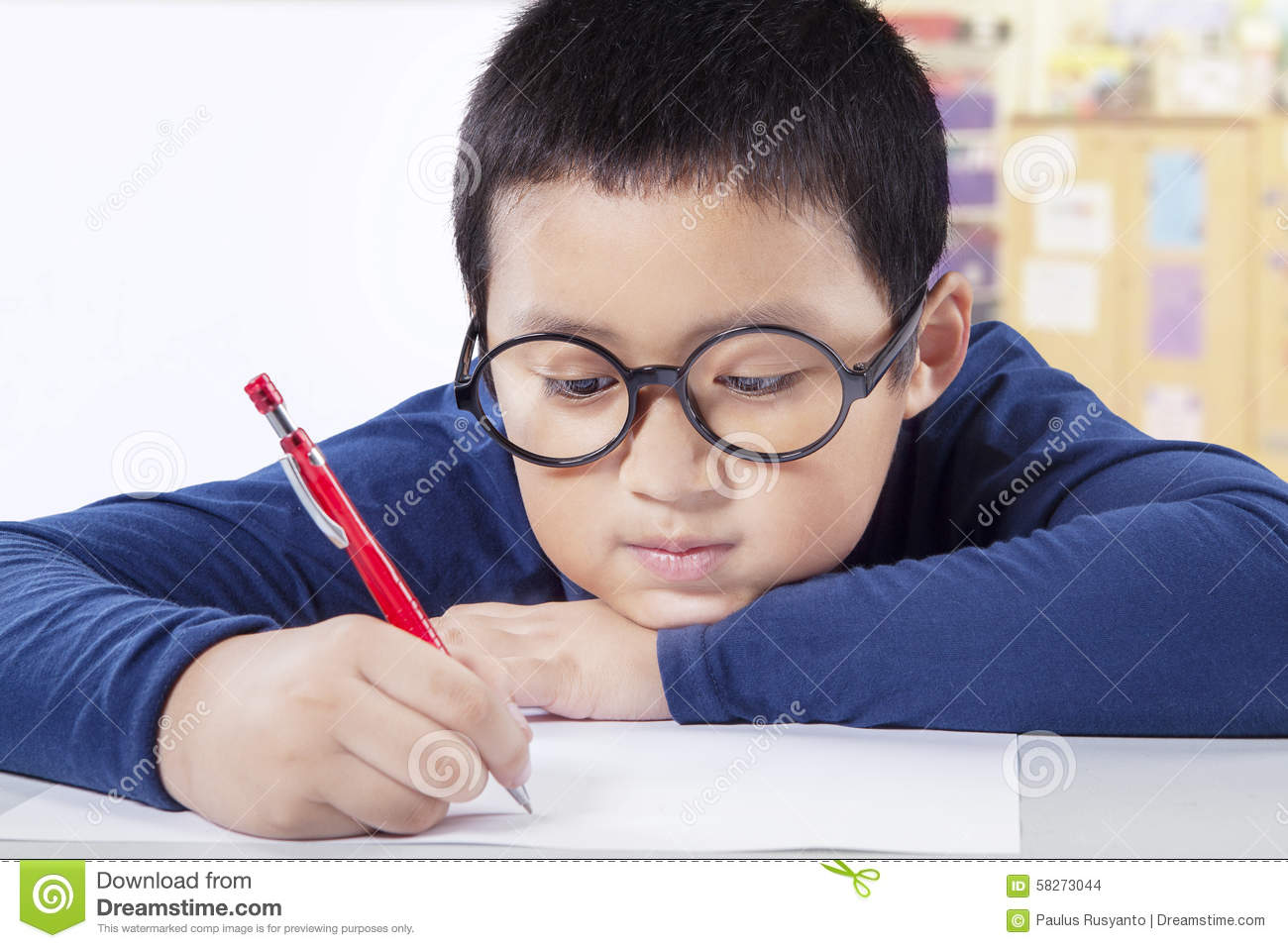 Cute Boy Writing On The Paper In Class Stock Photo