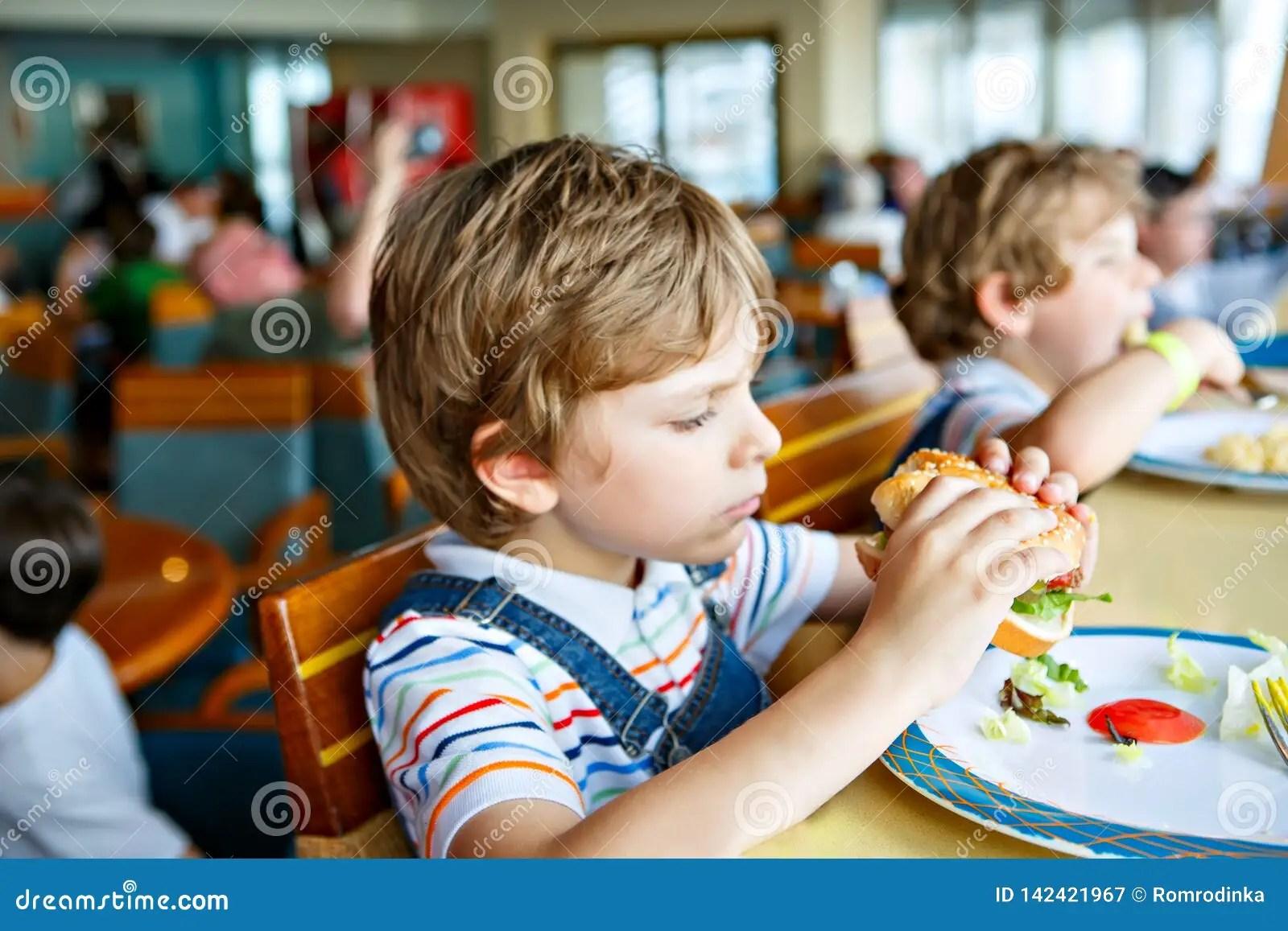 Cute Healthy Preschool Kid Boy Eats Hamburger Sitting In