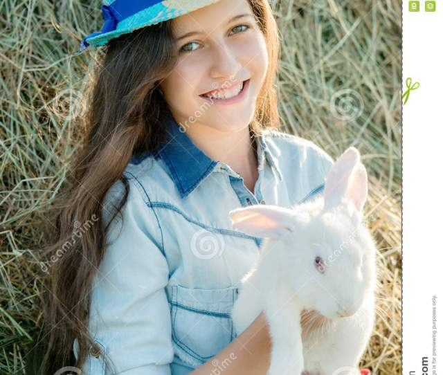 Cute Teen Girl With White Rabbit Sitting In Front Of Haystack