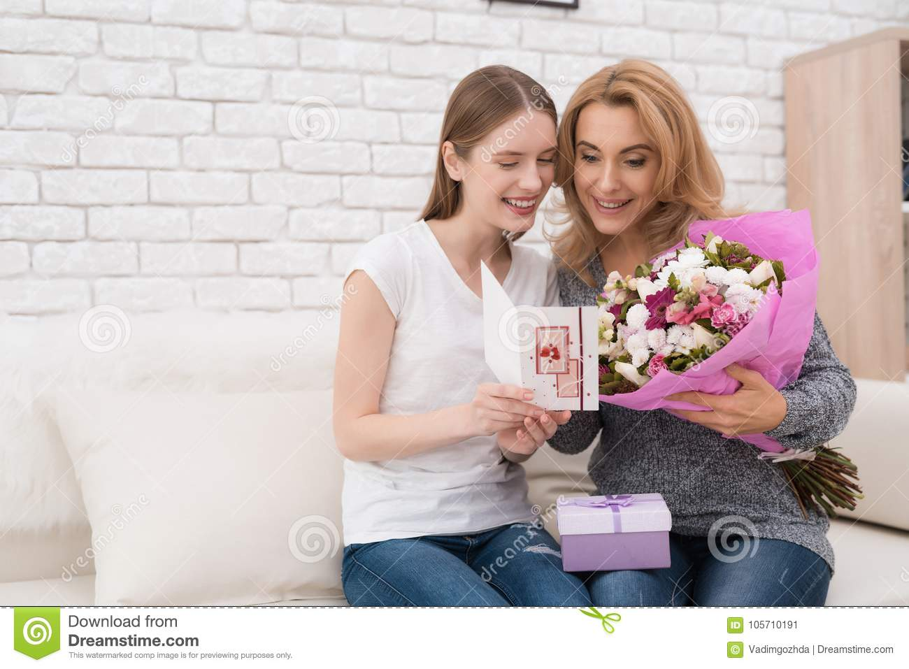 The Daughter Gives Her Mother Flowers And Ts Stock