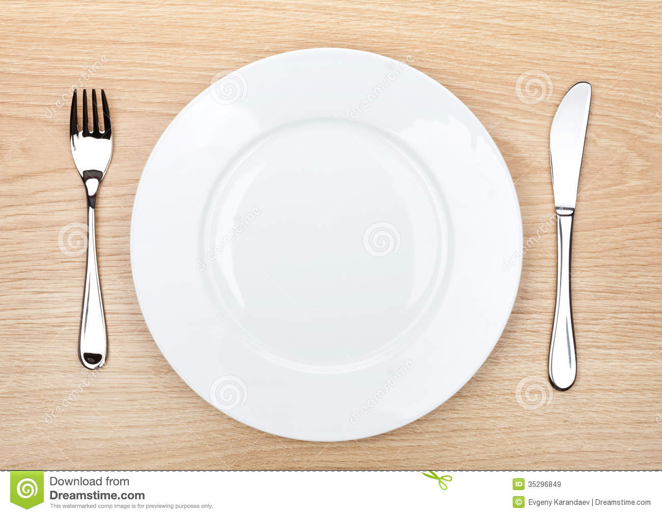 Empty White Plate With Silverware On Wooden Table Royalty