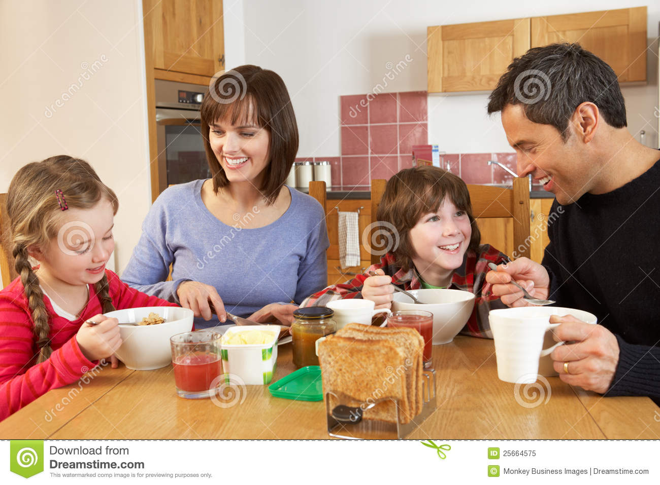 Family Eating Breakfast Together In Kitchen Royalty Free