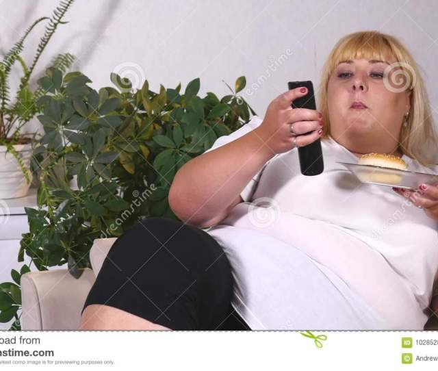 Fat Woman Eating A Burger Watching Tv And Laughes Stock Images