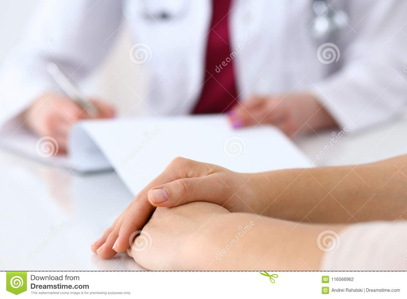 Female Doctor Filling Up An Application Form While