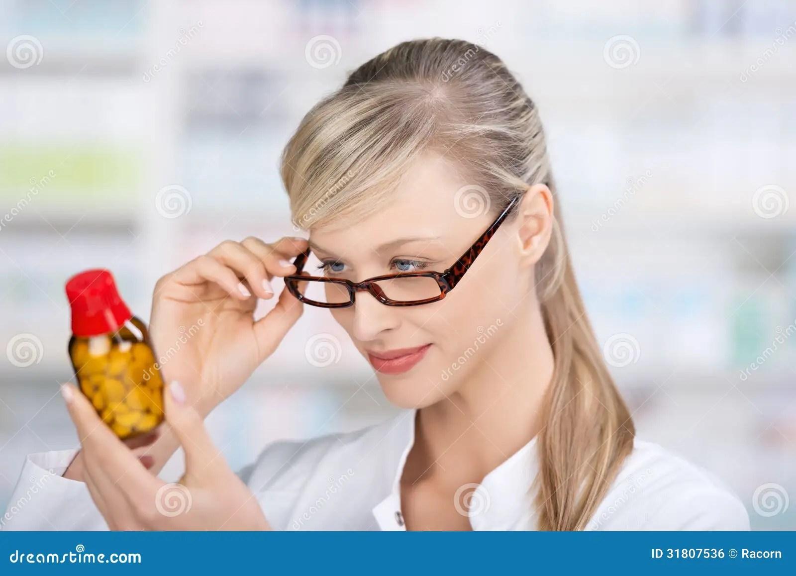 Female Pharmacist Reading The Medicine Label Stock Photo