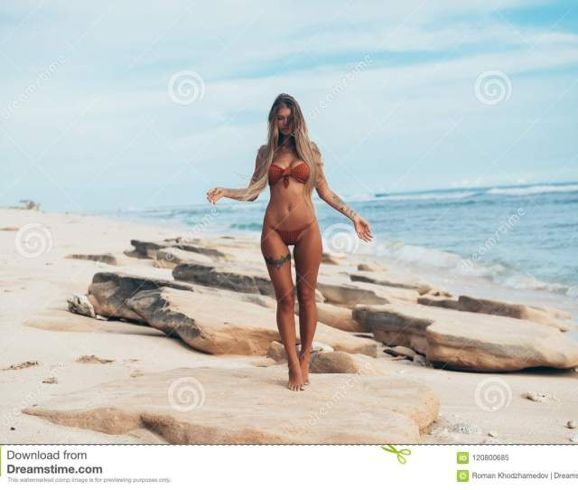 The Figure Sex Girl Climbed On Her Toes And Walks Gently Against A White Sandy Beach And Blue Sea Water Lightness Harmony Style Of Life Sport Concept
