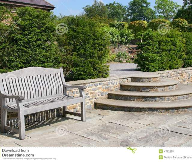 Outdoor Garden Tiled Patio Area With An Old Wooden Oak Bench Curved Steps To The Side And Shrubs To The Rear
