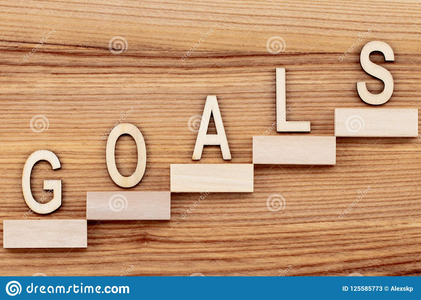 Goals Concept With Ladder Of Success On Wooden Table Stock