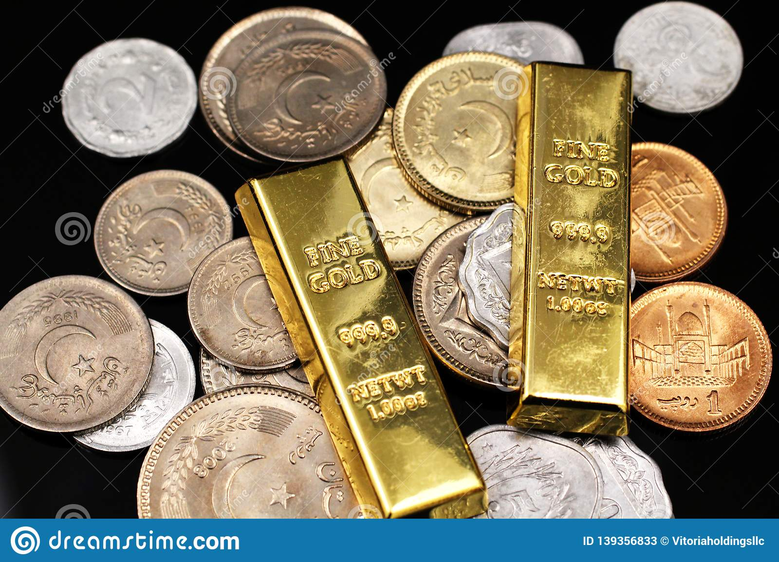 Gold One Ounce Ingots With Coins From Pakistan On A Black