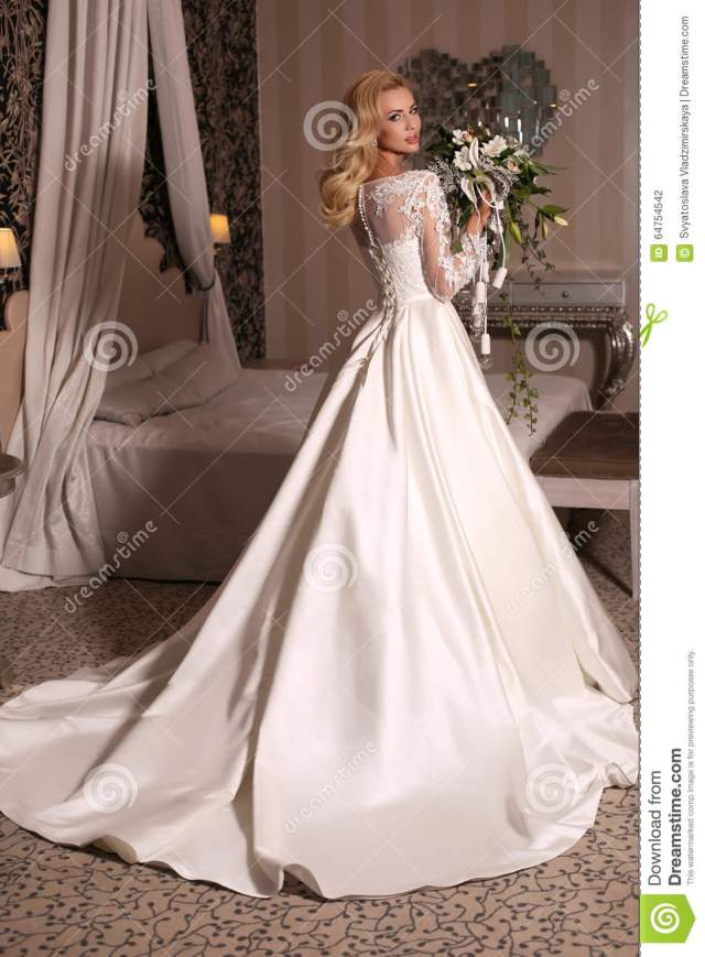 gorgeous woman with blond hair wears luxurious wedding dress