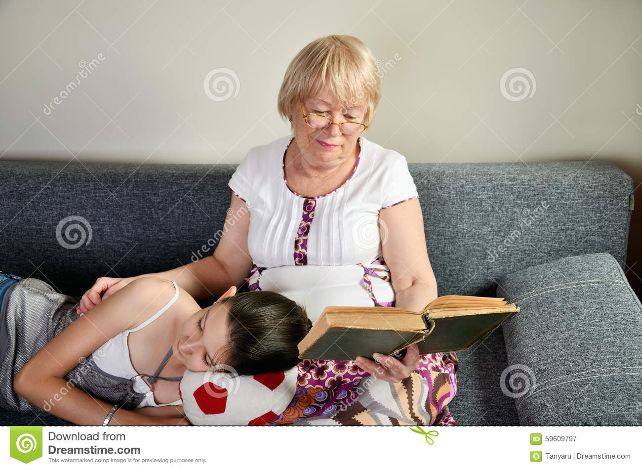 Granddaughter Asleep Near Her Reading Grandmother Stock Image