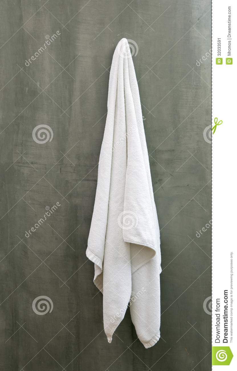Hanging White Towel Draped On Exposive Concrete Wall Stock