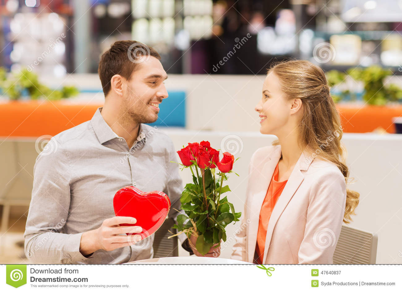 Happy Couple With Present And Flowers In Mall Stock Image