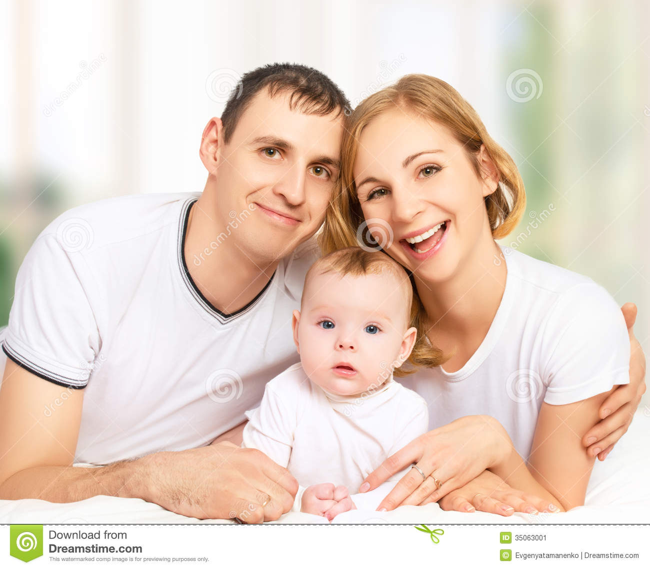 Happy Family Of Father Mother And Small Baby Girl