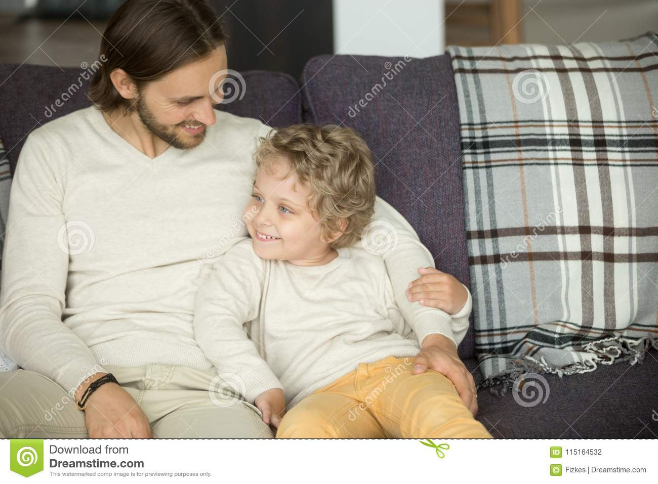 Happy Father Embracing Kid Son Sitting On Sofa At Home