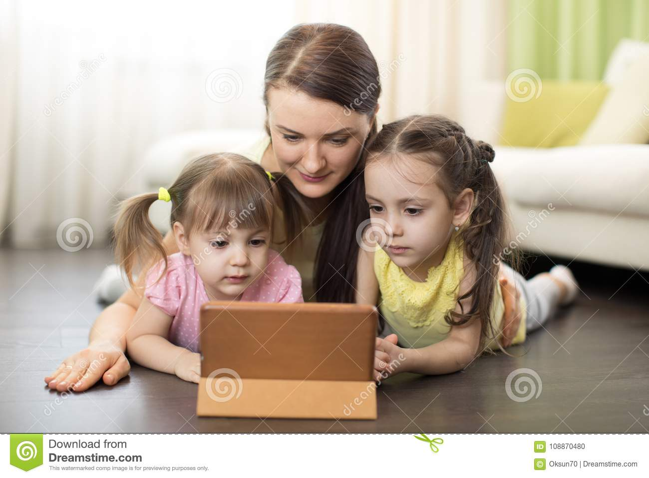 Happy Mother And Daughters Using Digital Tablet On Floor