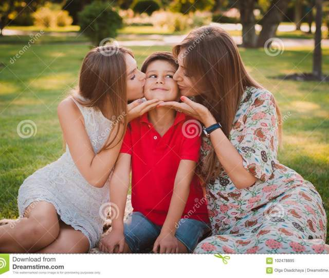 Happy Mother Son And Daughter In The Park Mom And Sister Kiss Their Son Happy Family Concept