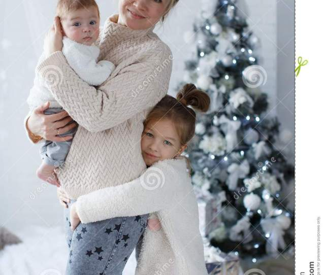 Happy Woman Cheerful Mother And Little Children A Girl And A Newborn Boy Sitting On A Fluffy White Blanket Beside The Christmas Festive Green Christmas