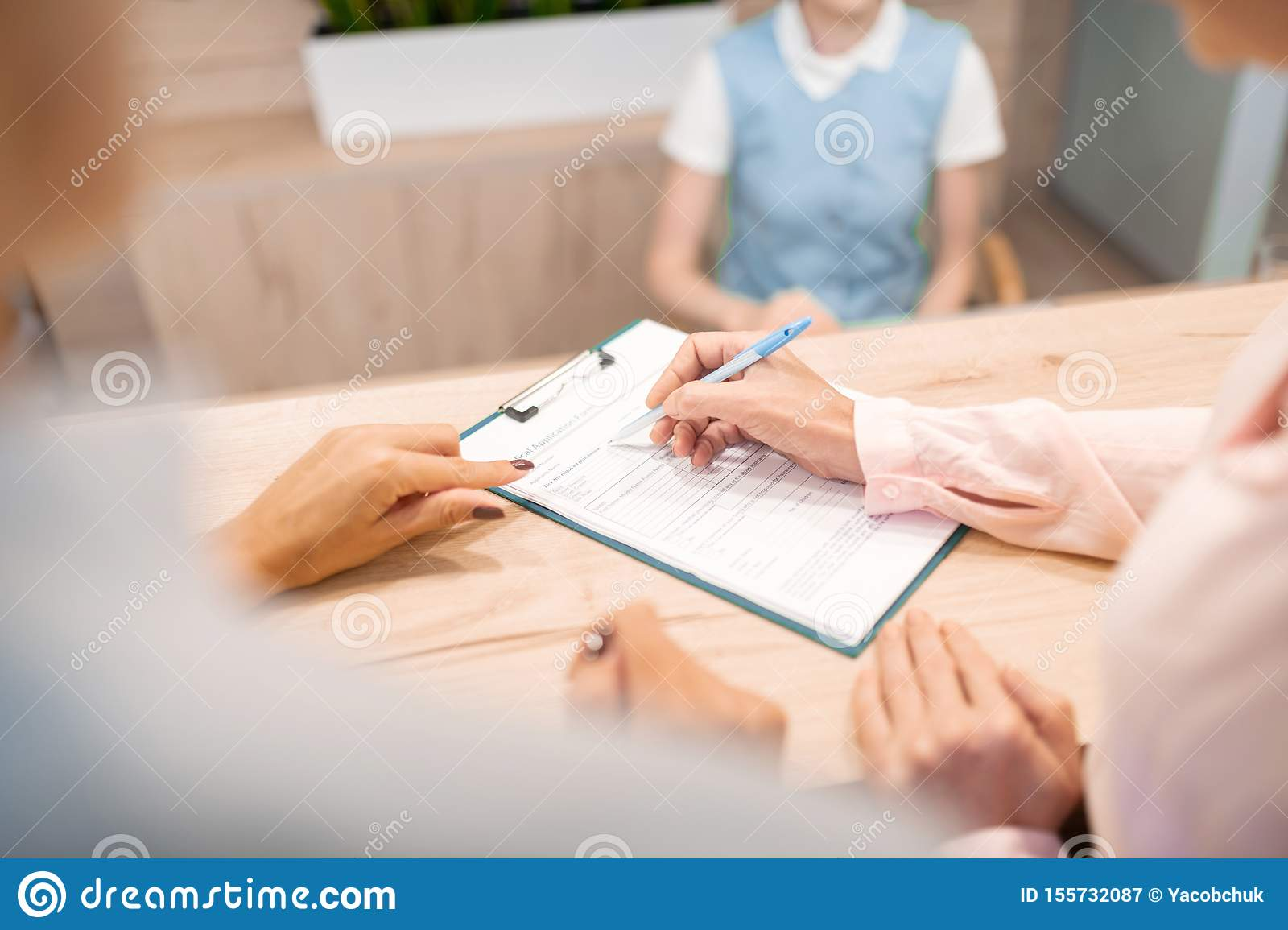 Doctor Pointing Her Patient Where To Sign The Form Stock
