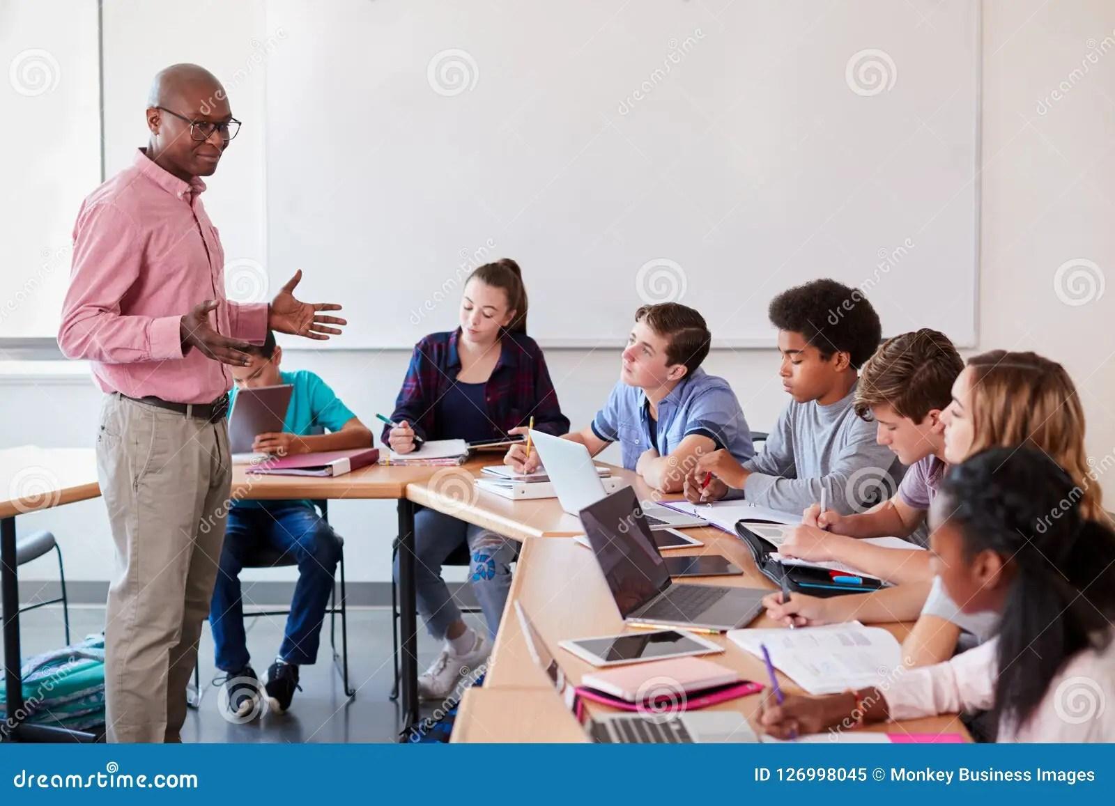High School Teacher Talking To Pupils Using Digital